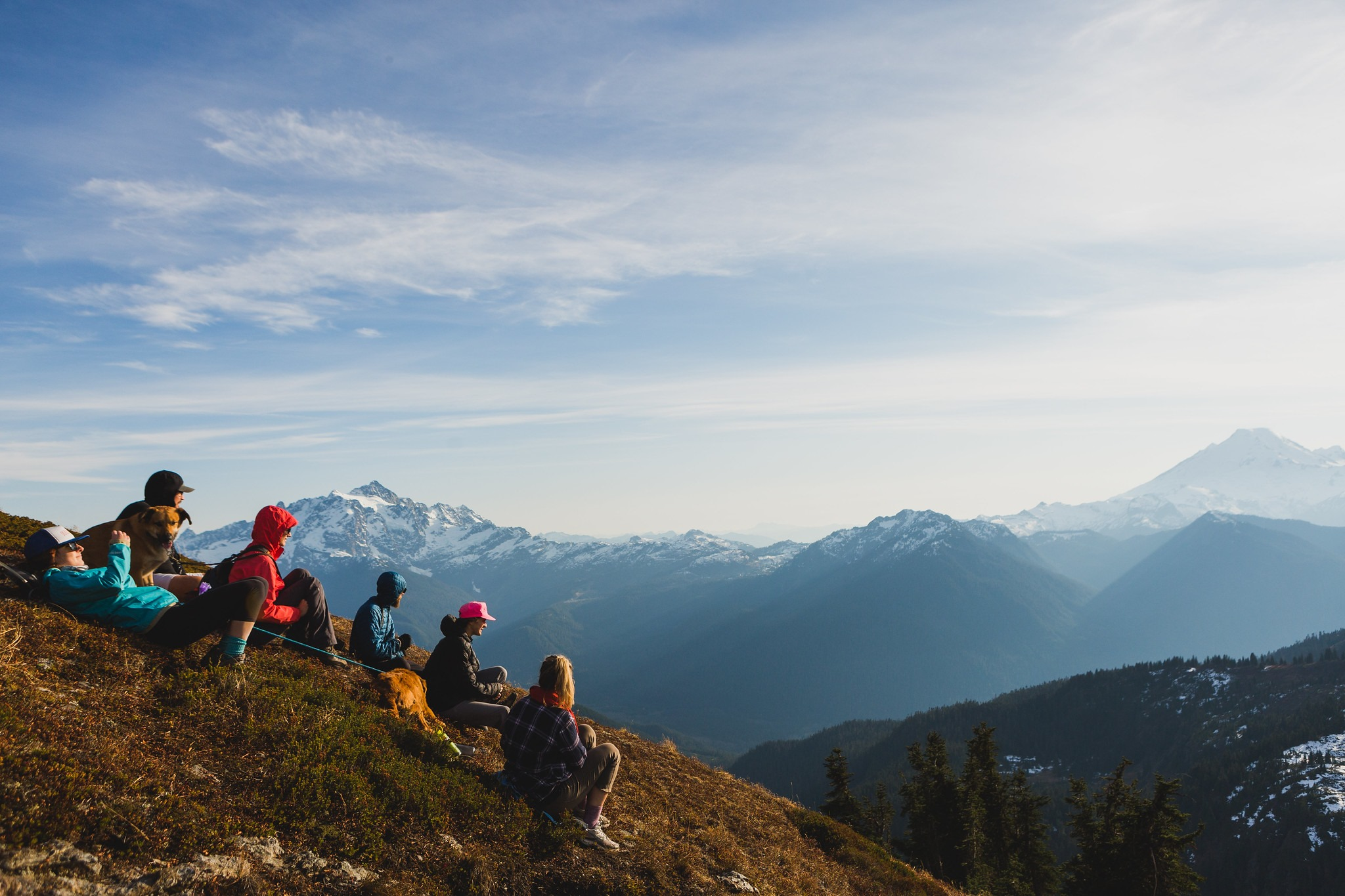 Students sitting on the summit of a mountain looking over a valley to the next mountain range